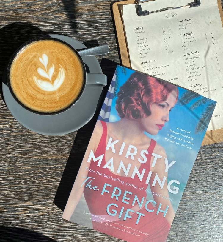 A copy of The French Gift by Kirsty Manning sits in a sunbeam on a wooden table with a cup of coffee next to it.