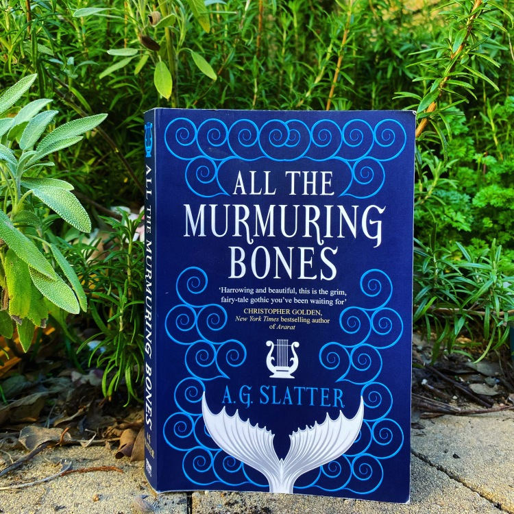 All the Murmuring Bones is pictured standing upright with the cover facing the camera. Right behind it in the background is a herb garden filled with parsley and sage and rosemary (and I'm sure there's some thyme too!)